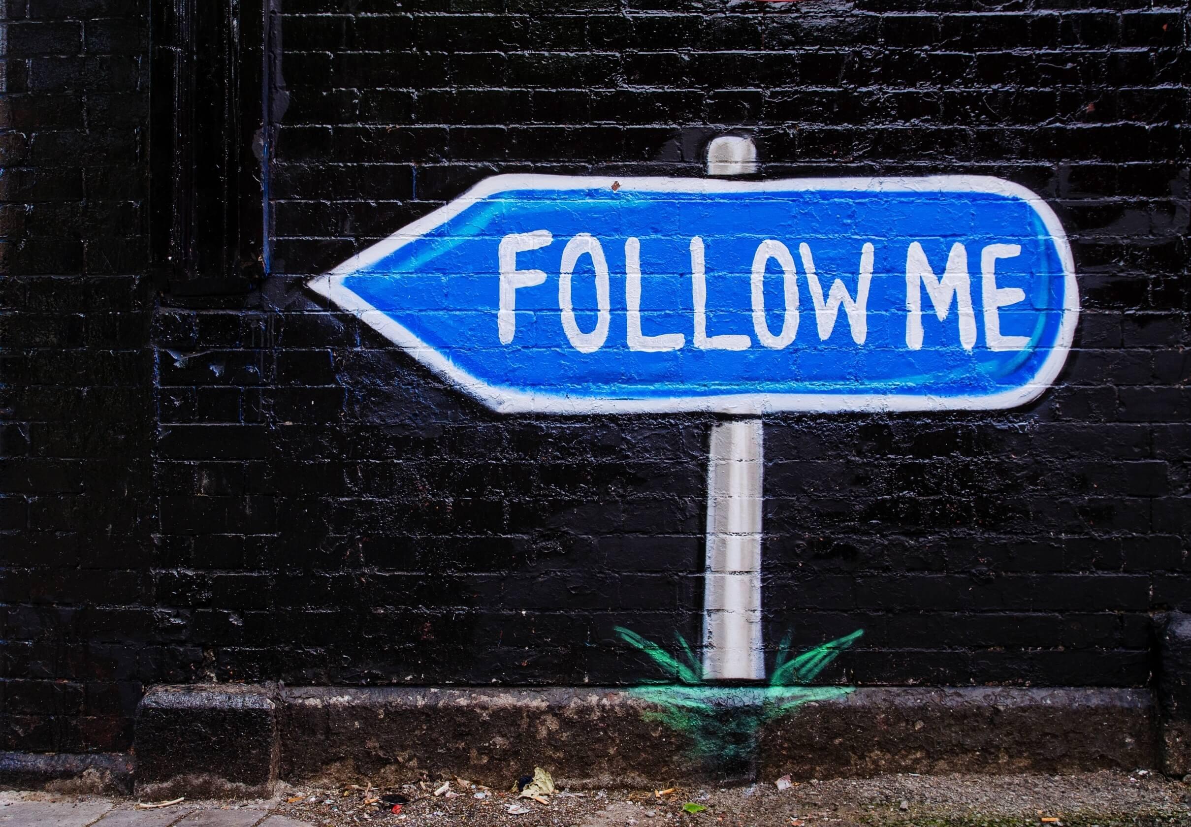 Follow me roadsign on black brick wall